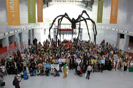Participants in the 2013 iEarn Conference and Youth Summit in Doha pose 30 foot spider sculpture by American artist Louise Bourgeois at the Qatar National Convention Center.